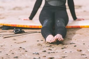 Low section of woman in wet suit with surfboard at beachの写真素材 [FYI00485562]