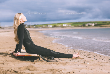 Beautiful blond in wet suit with surfboard at beachの写真素材 [FYI00485563]