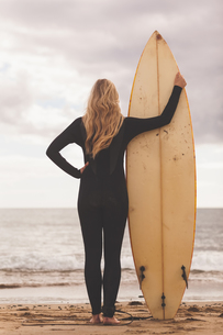Rear view of a blond in wet suit with surfboard at beachの写真素材 [FYI00485565]