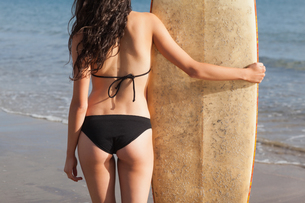 Mid section of a woman in bikini bottom with surfboard on beachの素材 [FYI00485571]