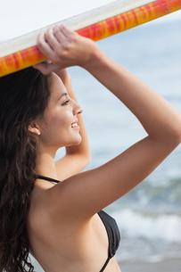 Bikini woman holding surfboard over head at beachの写真素材 [FYI00485576]
