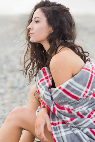 Serious woman covered with blanket at beachの写真素材 [FYI00485586]