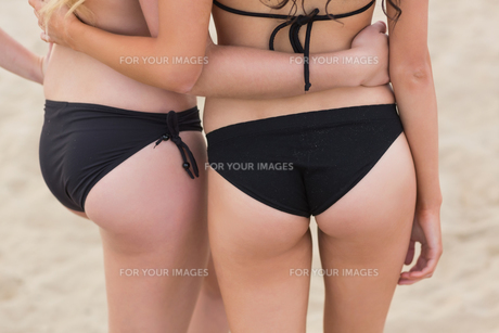 Mid section of two young bikini women at the beachの写真素材 [FYI00485590]