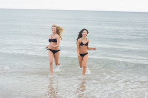Smiling bikini women running in water at beachの写真素材 [FYI00485595]