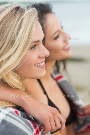 Two young women covered with blanket at beachの写真素材 [FYI00485599]