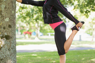 Side view of a woman stretching her leg during exercise at parkの写真素材 [FYI00485611]