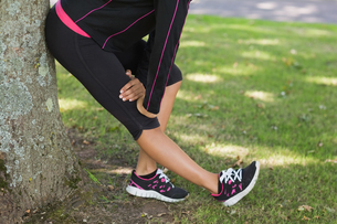 Low section of woman stretching her leg during exercise at parkの写真素材 [FYI00485614]