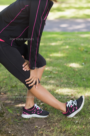 Mid section of woman stretching her leg during exercise at parkの素材 [FYI00485615]