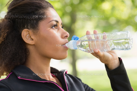 Close up side view of tired woman drinking water in parkの写真素材 [FYI00485616]