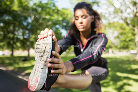 Pretty sporty woman stretching her leg in parkの写真素材 [FYI00485620]