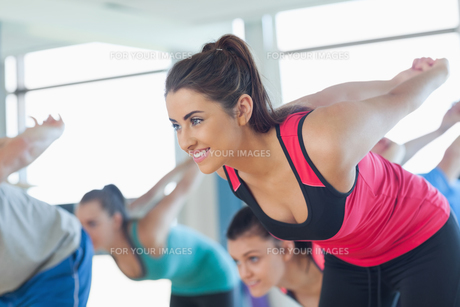 Smiling people doing power fitness exercise at yoga classの写真素材 [FYI00485621]
