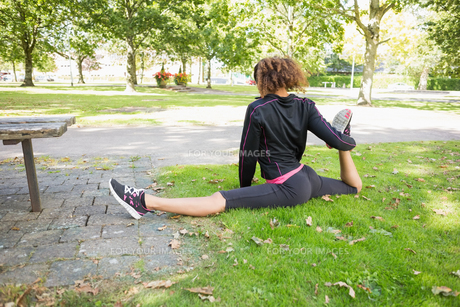 Flexible young woman doing the splits exercise in parkの写真素材 [FYI00485624]