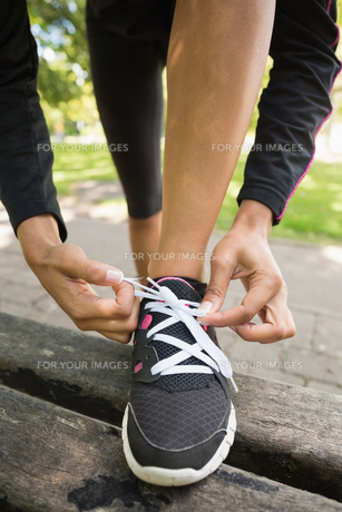 Close up low section of sporty woman wearing shoes in parkの写真素材 [FYI00485625]