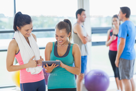 Fit women looking at digital table with friends chatting in backgroundの素材 [FYI00485627]
