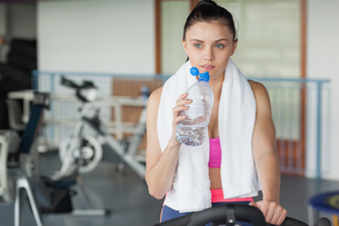 Woman drinking water while working out at spinning classの写真素材 [FYI00485628]