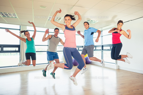 Fitness class and instructor jumping in fitness studioの素材 [FYI00485629]