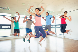 Fitness class and instructor jumping in fitness studioの写真素材 [FYI00485629]