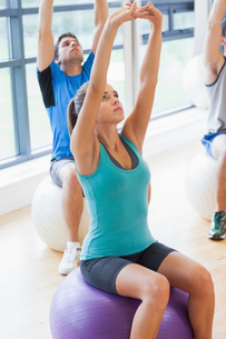 Sporty people stretching up hands on exercise balls at gymの写真素材 [FYI00485631]