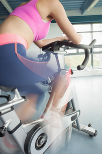 Determined young woman working out at spinning classの写真素材 [FYI00485633]