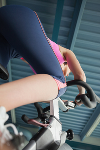 Determined young woman working out at spinning classの写真素材 [FYI00485634]
