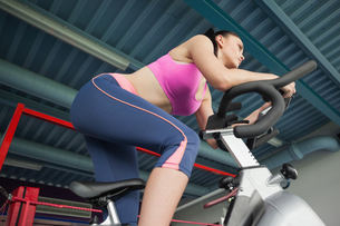 Determined young woman working out at spinning classの写真素材 [FYI00485636]