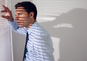 Businessman peeking through blinds in officeの写真素材 [FYI00485638]