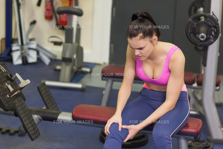 Healthy woman with an injured knee sitting in gymの写真素材 [FYI00485639]