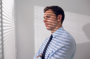 Businessman peeking through blinds in officeの写真素材 [FYI00485640]