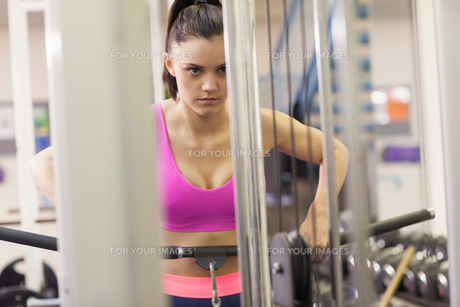 Determined woman doing exercises in gym on lat machineの写真素材 [FYI00485642]