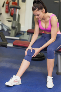 Healthy woman with an injured knee sitting in gymの写真素材 [FYI00485643]
