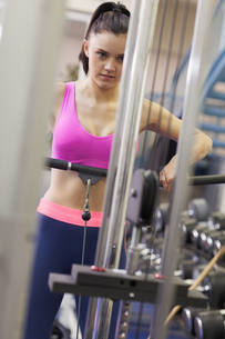 Determined woman doing exercises in gym on lat machineの写真素材 [FYI00485644]