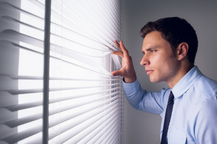 Businessman peeking through blinds in officeの写真素材 [FYI00485645]