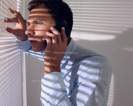 Businessman peeking through blinds while on call in officeの写真素材 [FYI00485646]
