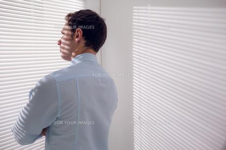 Businessman peeking through blinds in officeの素材 [FYI00485647]