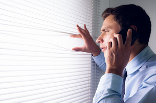 Businessman peeking through blinds while on call in officeの写真素材 [FYI00485648]