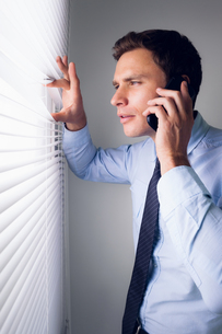 Businessman peeking through blinds while on call in officeの写真素材 [FYI00485652]