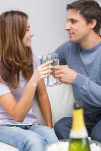 Romantic couple toasting flutes in the living roomの写真素材 [FYI00485656]