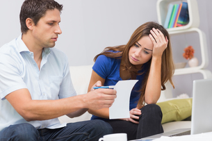Worried couple paying bills online with laptop at homeの写真素材 [FYI00485657]