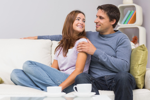 Loving couple looking at each other on sofa at homeの写真素材 [FYI00485658]