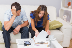 Worried couple paying their bills in living room at homeの写真素材 [FYI00485659]