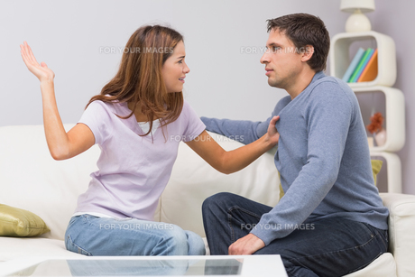 Young woman about to slap man in the living room at homeの写真素材 [FYI00485661]