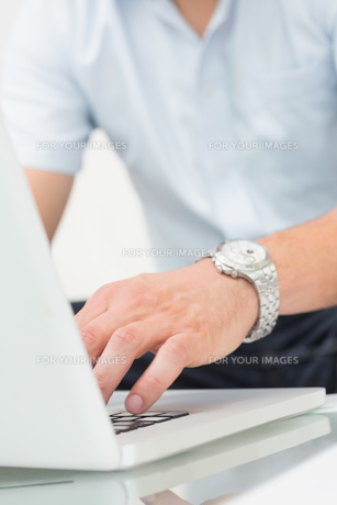 Mid section of a man using laptop on coffee tableの写真素材 [FYI00485663]