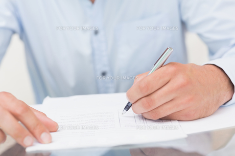 Mid section of a young man writing documentsの素材 [FYI00485670]
