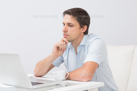Side view of a serious man using laptop at homeの素材 [FYI00485672]