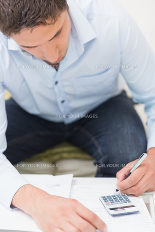 Closeup of a young man with bills and calculatorの素材 [FYI00485673]