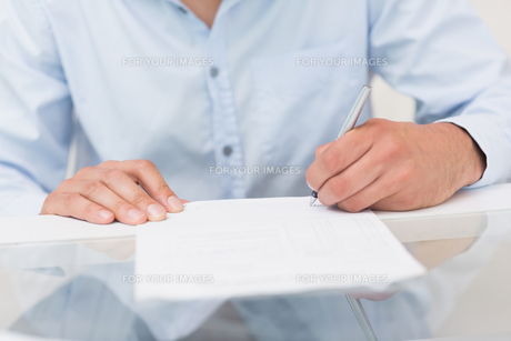 Closeup mid section of a man writing documentsの素材 [FYI00485674]