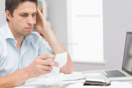 Worried man paying his bills online with laptop at homeの写真素材 [FYI00485675]