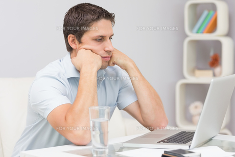 Serious young man using laptop in living roomの写真素材 [FYI00485676]