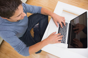 Overhead view of a man using laptop in living roomの写真素材 [FYI00485680]