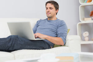 Relaxed young man using laptop in living roomの写真素材 [FYI00485681]